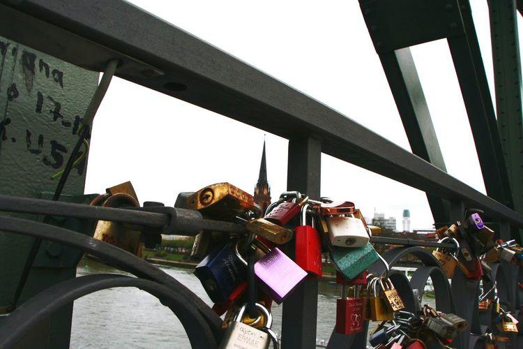 Padlocks hanging on bridge against sky