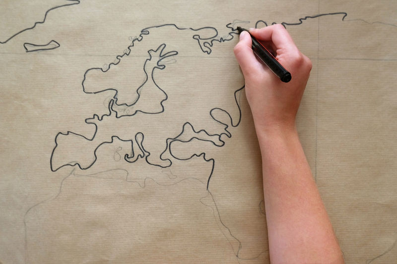 Close-up of hand drawing world map on paper