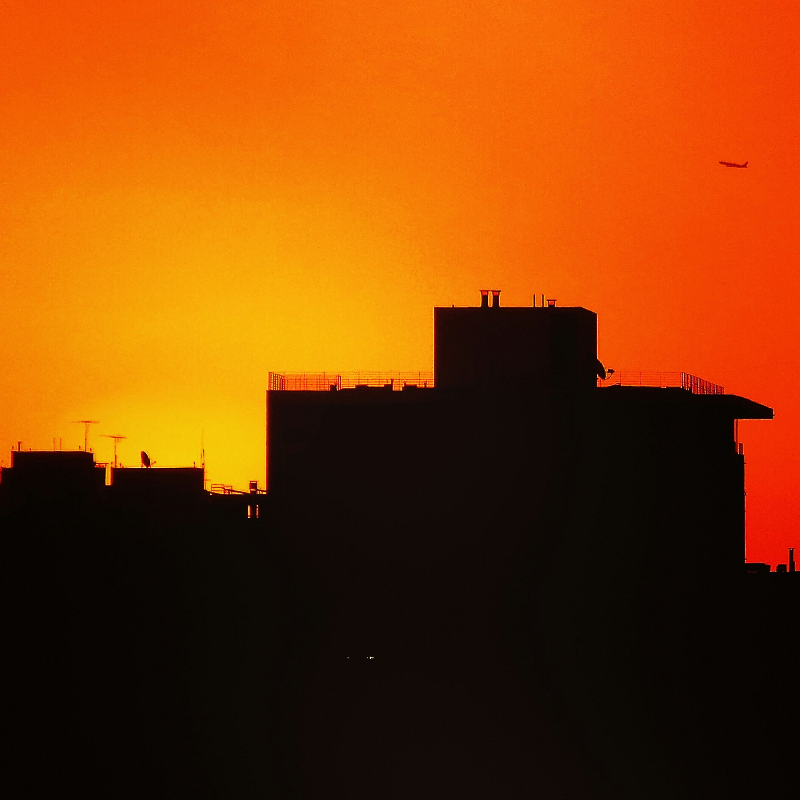 sunset, silhouette, architecture, building exterior, orange color, built structure, copy space, clear sky, low angle view, house, building, residential structure, outdoors, no people, high section, nature, residential building, sky, dusk, dark