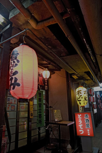 Red Lantern / Aka Chochin Tokyo Yurakucho Tokyo,Japan Yurakucho Aka C Aka Chochin Architecture Built Structure Communication Day Hanging Illuminated Indoors  Lantern Lighting Equipment Low Angle View No People Red Lantern Road Sign Text