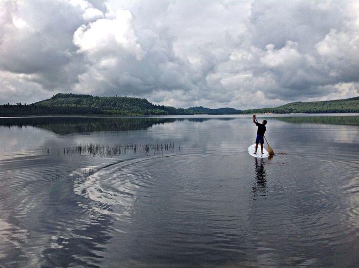 Man in calm lake against cloudy sky