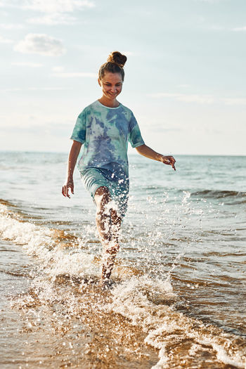 Girl splashing a water towards camera enjoying a free time over sea on a beach at sunset