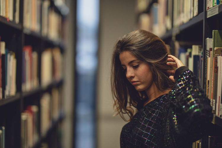 Side view of young woman looking away while standing at library