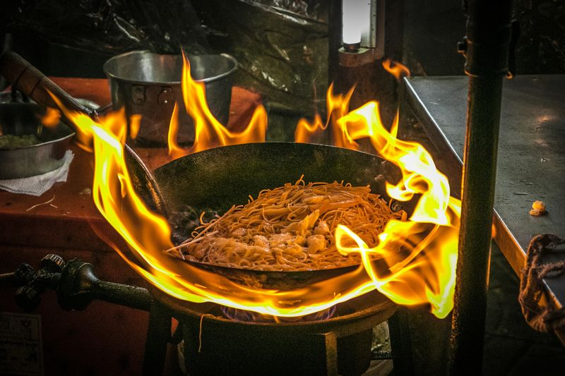 High Angle View Of Food Being Cooked At Stall
