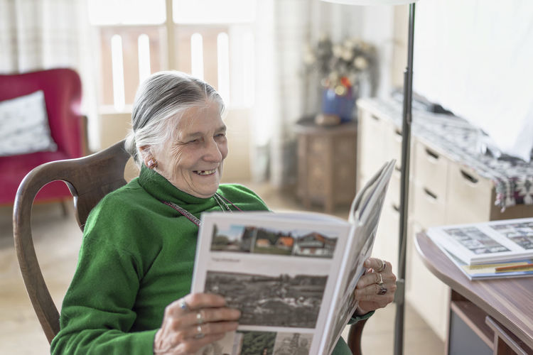 Adult Adults Only Aging Close-up Day Focus On Foreground Happiness Happy Holding Indoors  Leisure Activity Old Woman One Person One Senior Woman Only People Reading Real People Remembering Remembering Old Times Retirement Senior Adult Senior Woman Senior Women Smiling Women