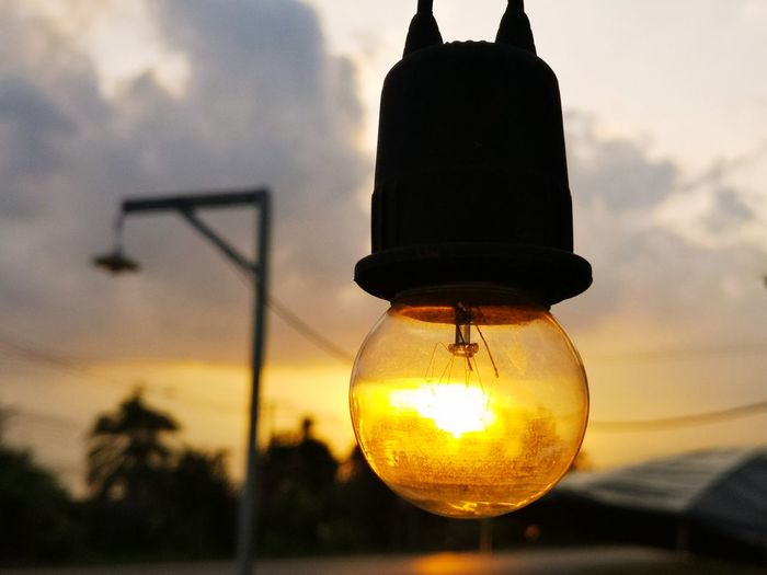 Low angle view of illuminated light bulb against sky at sunset