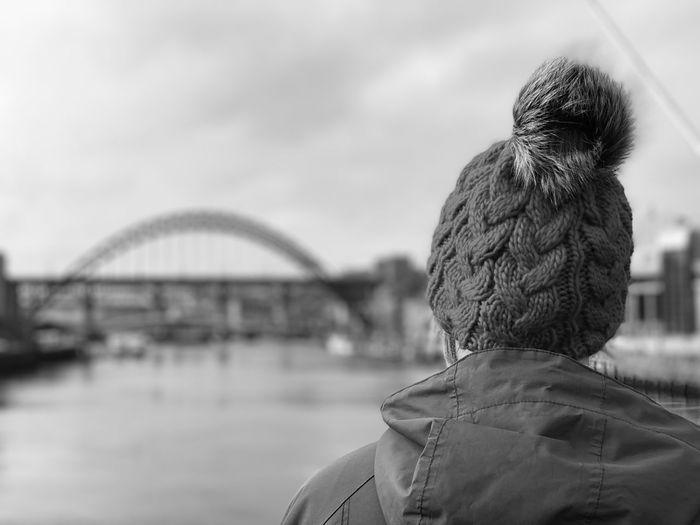 Rear view of man looking at bridge against sky