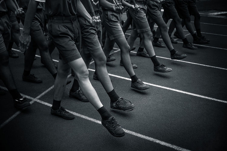 Low section of men marching on street in city