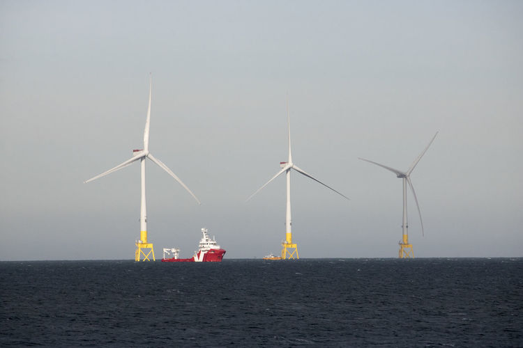 Windmills by sea against clear sky