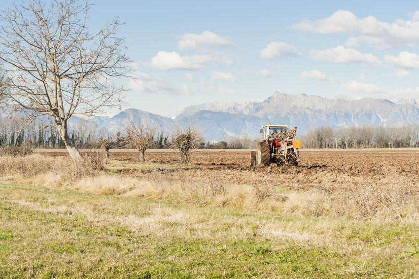 Agricultural landscape. With tractor plowing a field. The mountains in the background. Agriculture Combine Harvester Day Field Landscape Mountain Nature Outdoors Plow Rural Scene Scenics Sky Tool Tractor