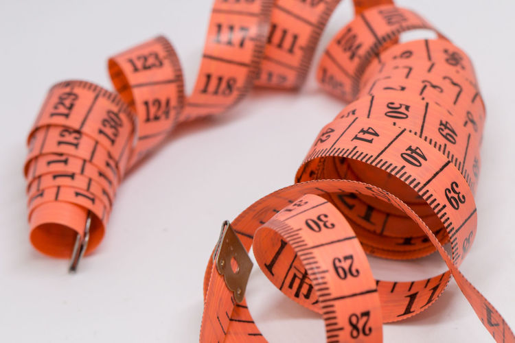 Close-up of tape measure over white background