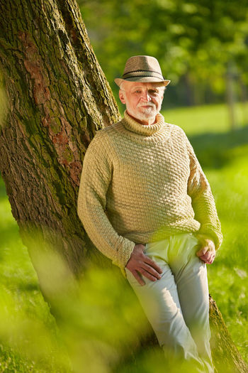 Portrait Of Senior Man Leaning On Tree Trunk At Park