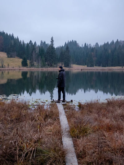 Man standing by lake against sky
