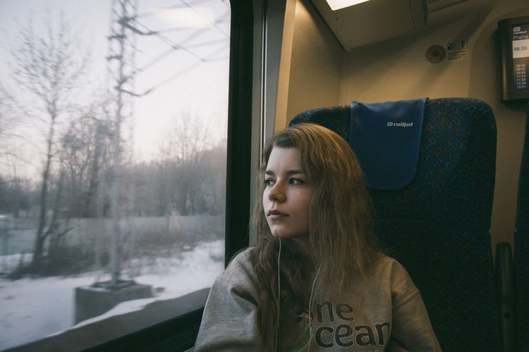 Adult Adults Only Beautiful Woman Day Headshot Journey Long Hair Looking Through Window Mode Of Transport One Person One Woman Only One Young Woman Only Only Women Passenger People Real People Sitting Transportation Travel Vehicle Interior Warm Clothing Window Women Young Adult Young Women