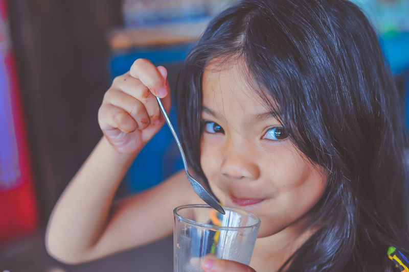 Close-Up Portrait Of Girl Drinking Juice While Sitting In Restaurant