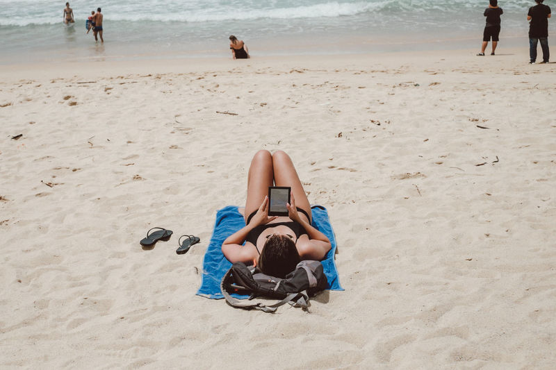 Woman Using Digital Tablet While Lying At Sandy Beach