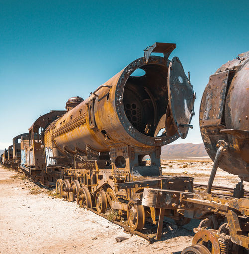 Abandoned train on railroad track against blue sky during sunny day