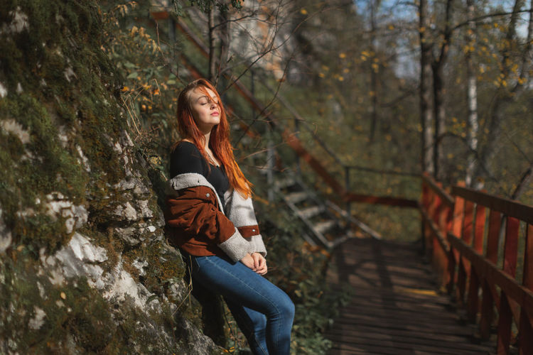 Woman with closed eyes standing by rock outdoors
