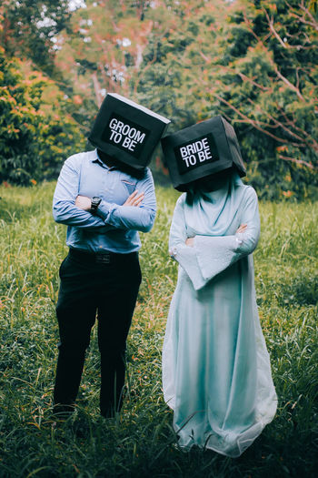 Couple wearing boxes with text while standing on field