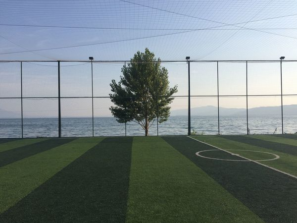 Football Pitch Tree Outdoors Sky Fence Water Mountain Landscape
