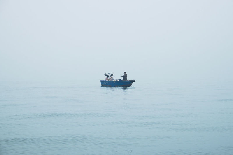 Alone Beauty In Nature Blue Boat Calm Fishing Fog Horizon Over Water Minimalism Nautical Vessel Ocean One Person Reflection Rippled Sailing Sea Seascape Tranquil Scene Transportation Travel Water