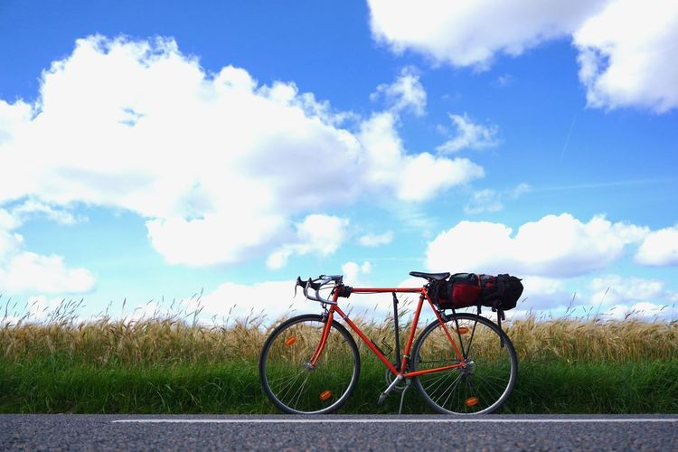 Bicycle on grass against sky