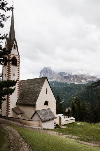 Church by buildings against sky