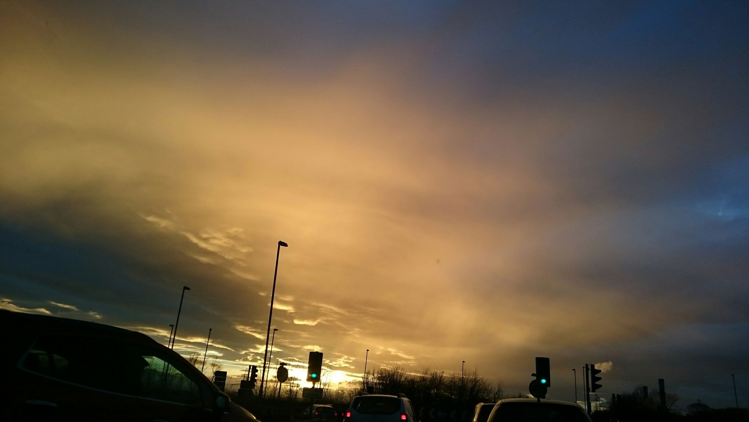 sky, cloud - sky, street light, transportation, car, building exterior, low angle view, sunset, built structure, silhouette, dusk, cloudy, land vehicle, mode of transport, architecture, city, cloud, overcast, weather, outdoors
