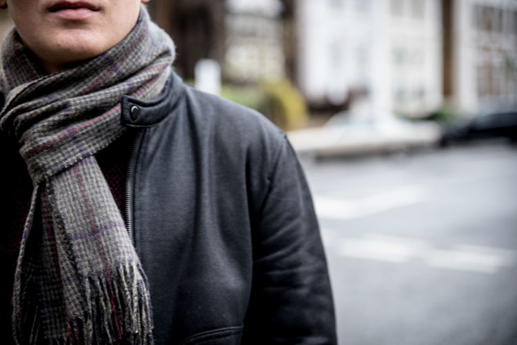 Midsection of man wearing scarf while standing on road