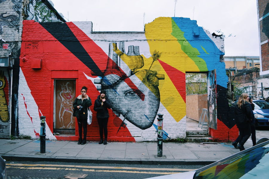 Street Art Art And Craft City Life Creativity Culture Full Length Holding Information Lifestyles Men Multi Colored Occupation Protection Real People Red Street Umbrella Urban Walking Women Art Is Everywhere Paint The Town Yellow