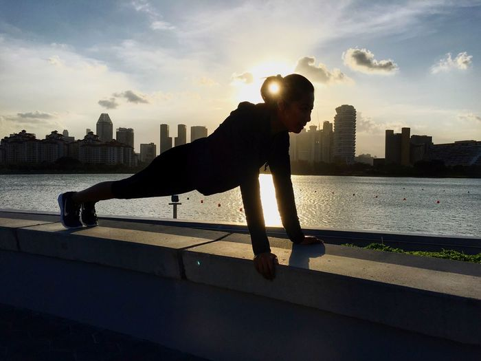 Woman Exercising On Retaining Wall By River In City During Sunset