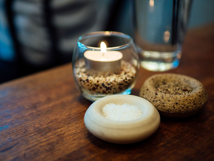 Close-Up Of Tea Light Candle And Seasoning On Wooden Table