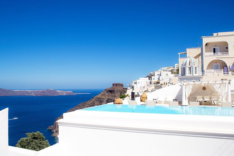 Infinity pool and buildings by sea against clear blue sky