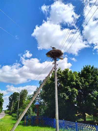 Low angle view of windmill on wooden post against sky