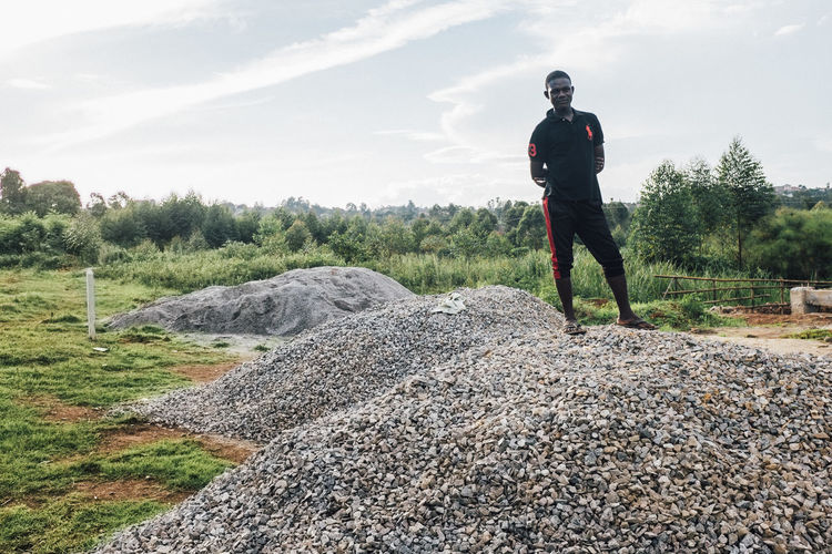 Africa African Building Building Materials Building Site Construction Construction Industry Construction Site Construction Work Dirt Dirty Gravel Heap Man Men Outdoors Pile Portrait Stack Standing Stone Stones Work Worker Working