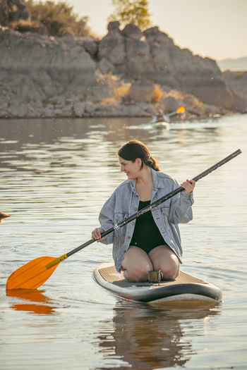 Full length of woman sitting in lake
