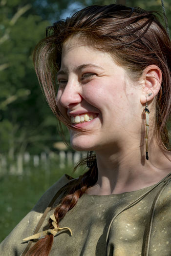 Close-up of smiling young woman looking away outdoors