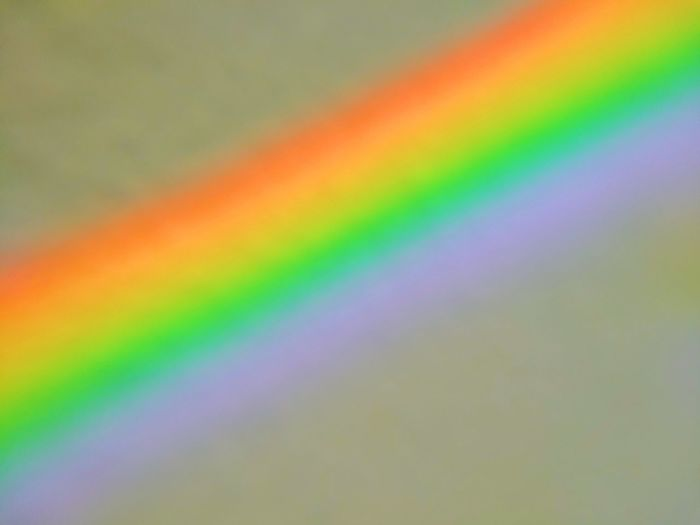 Defocused image of rainbow over colored background
