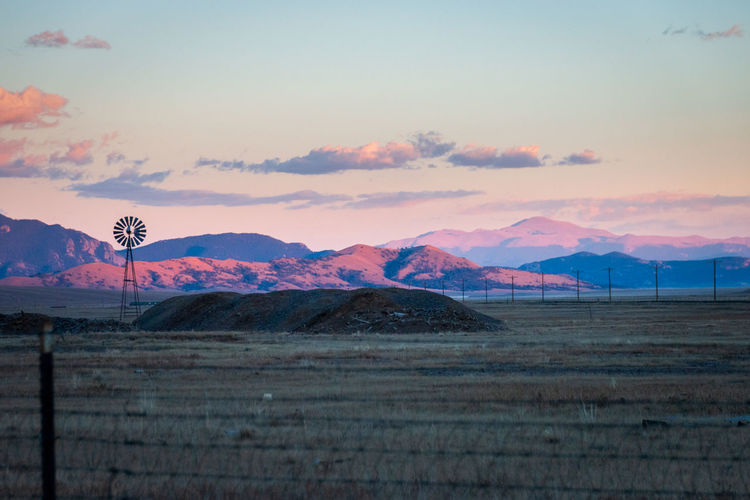 Wind turbines on land against pikes peak and sky during sunset
