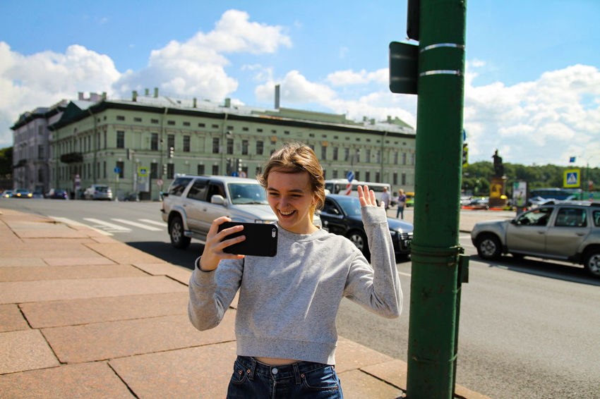 Happy girl recording a video TheWeekOnEyeEM Car Casual Clothing Cloud - Sky Cute Day Front View Girl Happiness Holding Mobile Phone One Person Outdoors Photographing Real People Selfie Sky Smart Phone Smiling Standing Street Technology Transportation Using Phone Young Adult