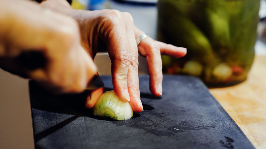 Cropped Hands Chopping Onion