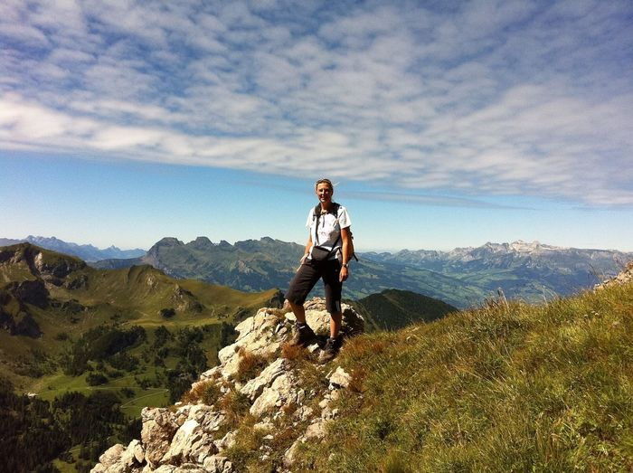 Happy female hiker standing on field at mountains against sky