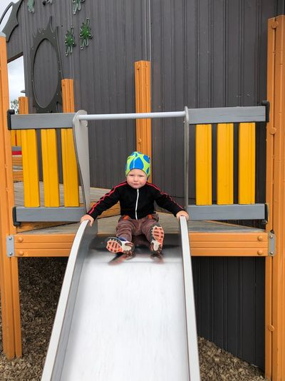 Portrait of boy sitting on slide at playground
