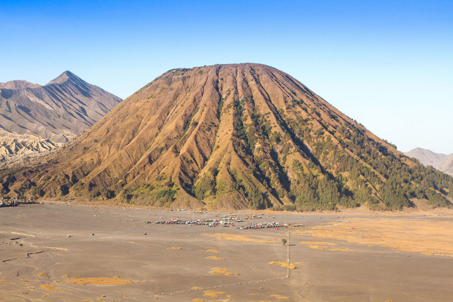 Layer Volcanic ash as sand ground of Mount Bromo volcano the magnificent view of Mt. Bromo located in Bromo Tengger Semeru National Park, East Java, Indonesia. Beauty In Nature Blue Clear Sky Day Geology Majestic Mountain Mountain Range Natural Landmark Nature Non-urban Scene Outdoors Physical Geography Remote Rock Formation Rocky Scenics Solitude Tranquil Scene Tranquility Water Waterfront