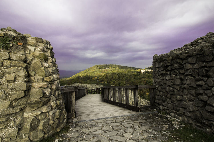 View of stone wall against cloudy sky