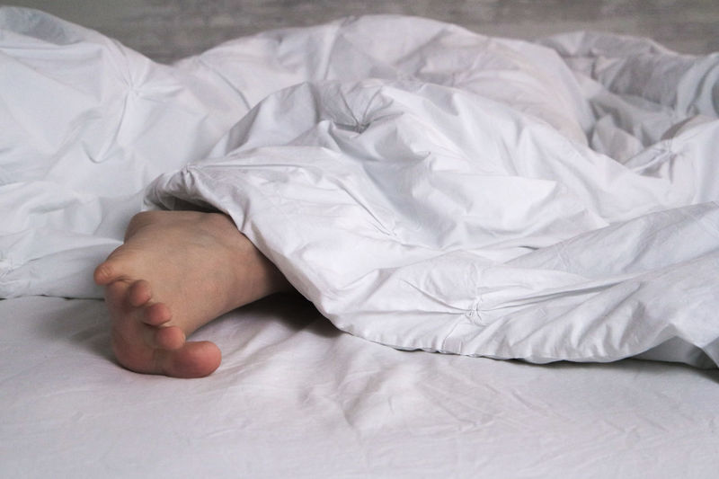 Low Section Of Woman Lying Under Blanket