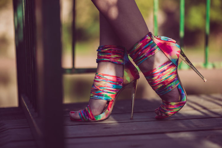 Low section of woman wearing colorful stilettos