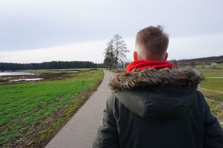 Rear view of man standing landscape against sky during winter