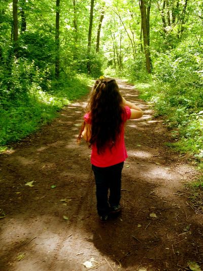 Rear view of woman walking on footpath in forest