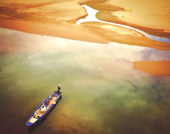 """I took this photo when i visited my father's hometown. He took me to this river so that I could make some beautiful river-view-pictures. But out of my father's expectations, this river was strongly polluted by the sand excavation. Oil was floating, the river was narrowing. However, the special color of the river reminded me the galaxy, which means """"silver river"""" in Chinese. Aerial View Environment Environmental Damage Environmental Protection High Angle View Nature Nautical Vessel No People Outdoors Sky Transportation Water First Eyeem Photo"""